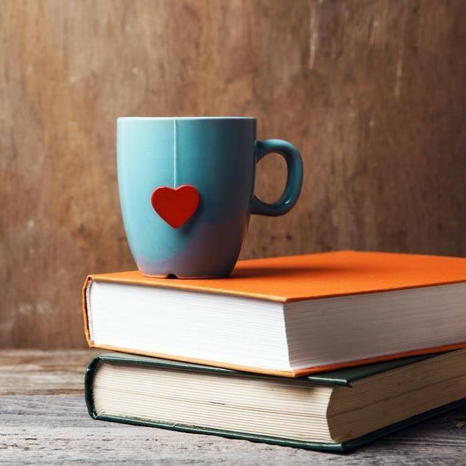 Two books on top of one another, with a mug resting on top of them, and a tea-bag paper label in the shape of a red heart dangling outside the cup